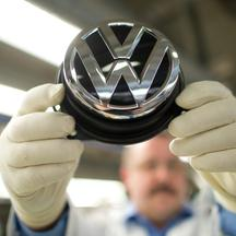 An employee holds a Volkswagen logo in the production street for the Golf VII at the Volkswagen plant in Wolfsburg, Germany, 25 February 2013. Photo: Julian Stratenschulte/DPA/PIXSELL
