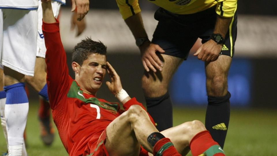 'Cristiano Ronaldo of Portugal grimaces next to referee Howard Webb after being tackled during the Euro 2012 play-off first leg qualifying soccer match against Bosnia in the town of Zenica November 11