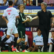 'Real Madrid's coach Jose Mourinho (R) gives the ball to Real Madrid's Luka Modric (C) during the Spanish league football match between Sevilla FC and Real Madrid on September 15, 2012 at the Ramon