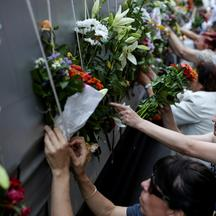 Women place flowers on a truck carrying coffins of newly identified victims of the 1995 Srebrenica massacre, in front of the presidential building in Sarajevo, Bosnia and Herzegovina, July 9, 2016. REUTERS/Dado Ruvic