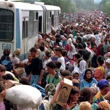 'File picture shows around 10,000 refugees from Srebrenica boarding buses at a camp outside the UN base at Tuzla airport, July 14, 1995. Bosnian Serb general Ratko Mladic made a throat-slitting gestur