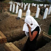 'A Bosnian Muslim woman cries near a new open grave with the coffin of her relative, which was prepared for a mass burial at the Memorial Center in Potocari, near Srebrenica July 10, 2012. The bodies