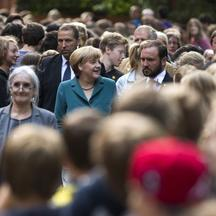 'German Chancellor Angela Merkel (C) arrives for a visit to the Heinz Schliemann grammar school in Berlin August 13, 2013. Merkel on Tuesday delivered a guest history lecture on the erection of the Be