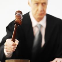 'Close-up of male judge banging gavel'